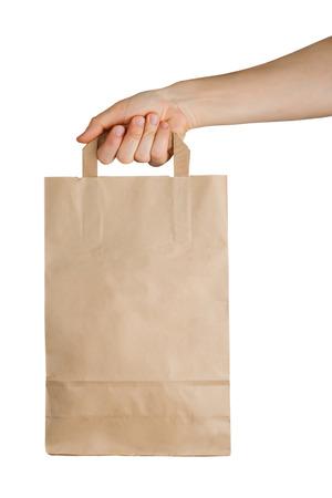 白い背景で隔離の紙袋を持っている手。配信の概念