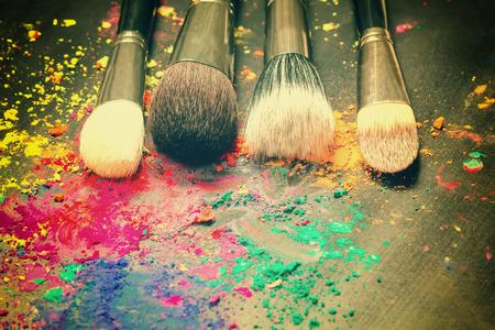 the brush: Cepillos del maquillaje en un fondo del polvo colorido. Imagen entonada