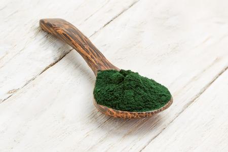 algae: Organic spirulina algae powder in wooden spoon