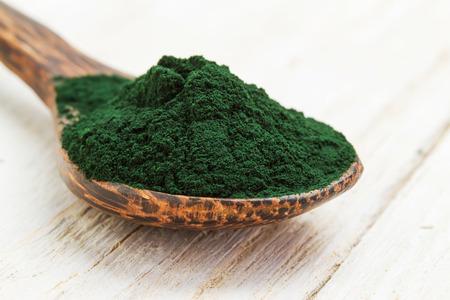 木のスプーンで有機スピルリナ藻類粉末のクローズ アップ 写真素材