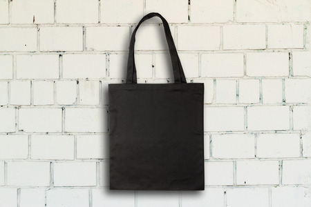 Black fabric bag against vintage brick wall Reklamní fotografie