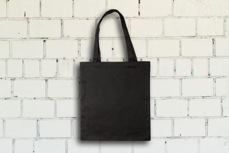 fabric bag: Black fabric bag against vintage brick wall Stock Photo