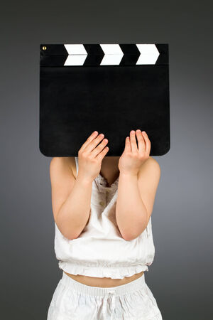Kid holding blank clapper board with copyspace photo