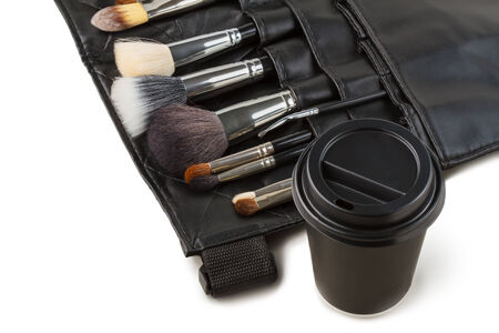Makeup brushes and a coffee cup. Coffee break from work. photo