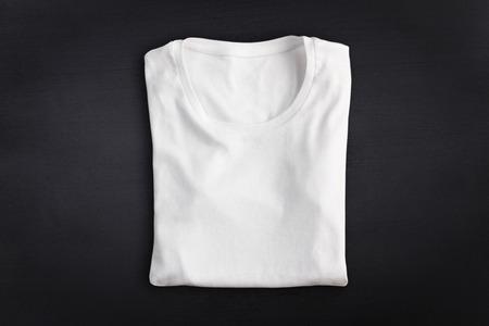 Blank folded t-shirt against chalkboard background 写真素材