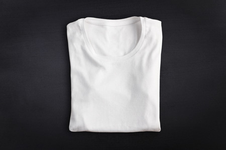 blank t shirt: Blank folded t-shirt against chalkboard background Stock Photo