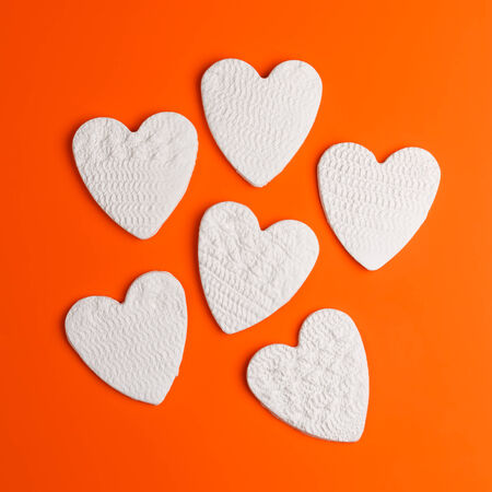 kaolin: Handmade little hearts made of pottery clay against orange background