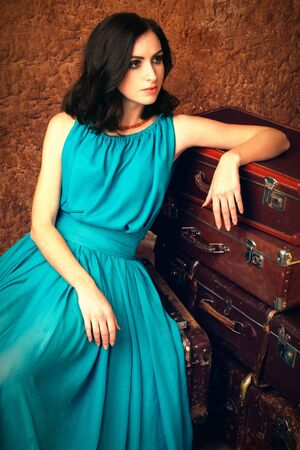 Attractive woman sitting next the pile of vintage suitcases photo