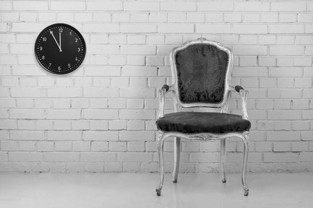 Vintage armchair against brick wall with clock. Converted in B&W photo