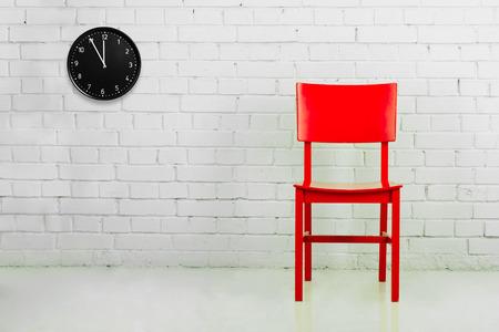 時計とれんが造りの白い壁に赤い椅子