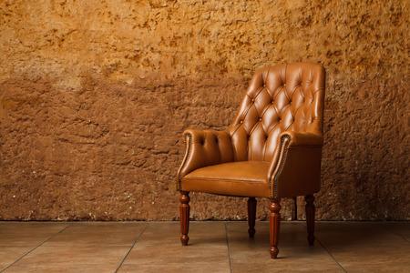 Kožené křeslo proti kamenné zdi. Vintage křeslo v podkroví.