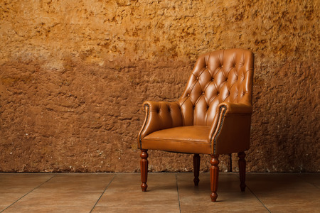 living room furniture: Leather armchair against stone wall. Vintage armchair in loft. Stock Photo