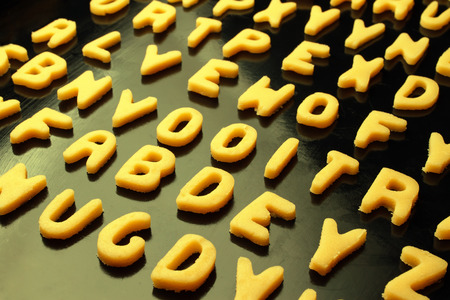 Alphabet cookies on baking pan. Toned effect photo