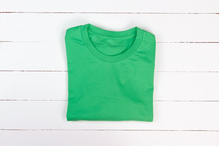 Green folded t-shirt on white wooden background