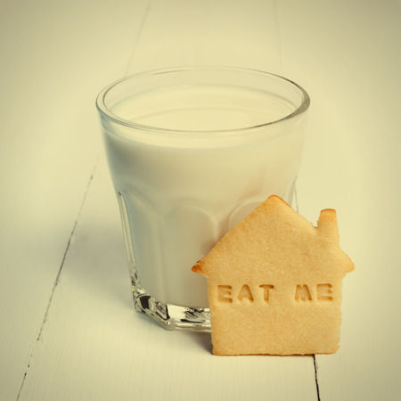 drink me: Glass of milk and cookie with sign EAT ME against white wooden background Stock Photo