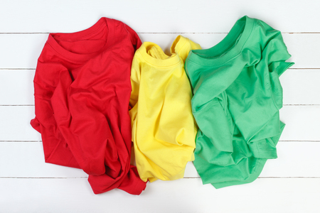 slovenly: Red, green and yellow careless folded t-shirts on white wooden background