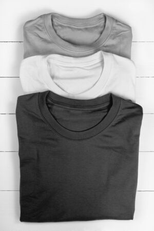 converted: Three folded t-shirts. Converted in black and white