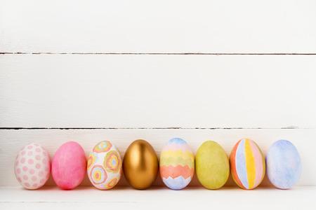 huevo blanco: Huevos de Pascua decorados en un fondo blanco con espacio de copia Foto de archivo