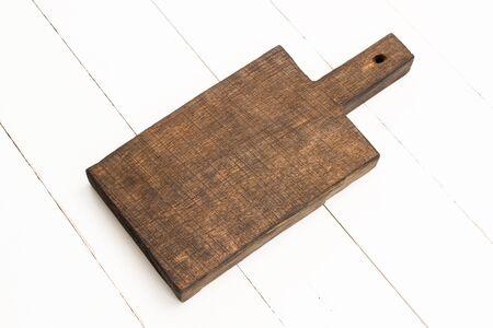 oaken: Wooden oaken chopping board on white wooden table Stock Photo