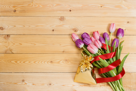 gloden: Tulip bouquet with red ribbon and gift in gloden bag on natural wooden texture