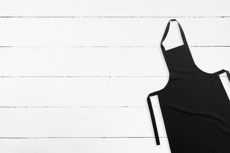 mandil: Delantal negro en blanco sobre fondo de madera blanca con espacio de copia