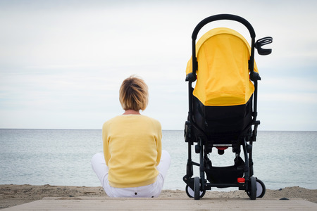 Donna che guarda attraverso il mare mentre si siede sulla spiaggia con il carrello del bambino. Giovane madre seduta all'aperto con il passeggino. Concetto di maternità con copyspace