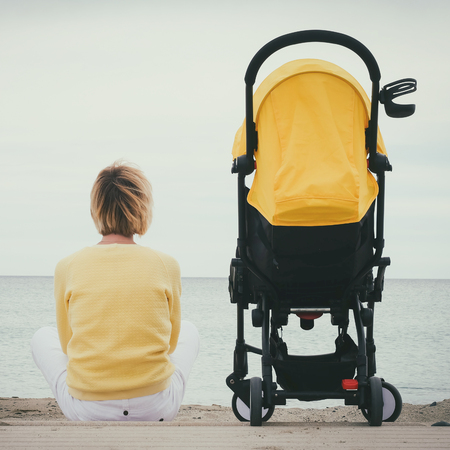 Woman sitting by the sea with baby carriage. Young mother sitting outdoor with stroller. Maternity concept