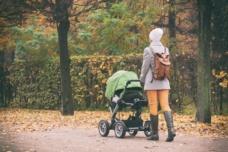 autumn young: Young mother pushing stroller in autumn park. Young woman strolling with baby in green buggy outdoors Stock Photo