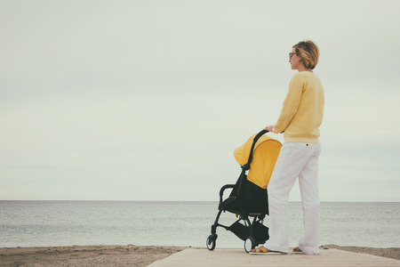 Young mother stand with stroller by the sea. Young mother outdoors. Maternity concept image with copyspace