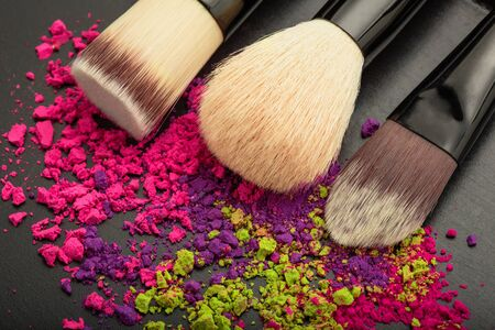 Closeup of makeup brushes with colorful makeup eyeshadow texture