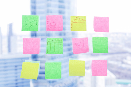 Colorful sticky notes on window in the office with skyscrapers on background