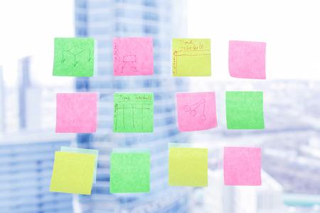Kleurrijke kleverige nota's over venster in het bureau met wolkenkrabbers op achtergrond