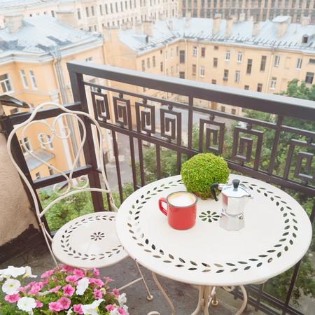 Coffee table with chair on balcony. Coffee mug with coffee maker outdoor