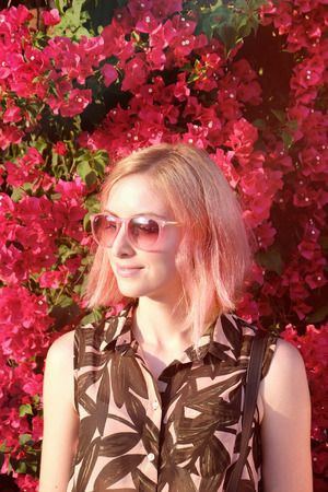 Young woman with pink hair color posing outdoor with flowers