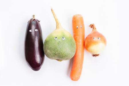 食品野菜のコンセプト。茄子、緑大根、人参、葱の白い背景の上の漫画の目。面白い食べ物のコンセプトです。トップ ビュー 写真素材