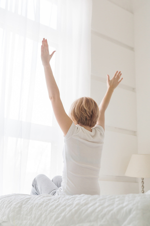 Rear view of young woman sitting on bed with hands raised up in the morning in white bedroom