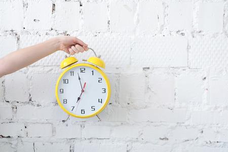 Woman hand holding alarm clock against white blank brick wall