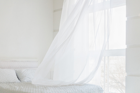 White waving curtain in white bedroom with window