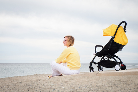 Woman looking through the sea while sitting on beach with stroller Stock Photo