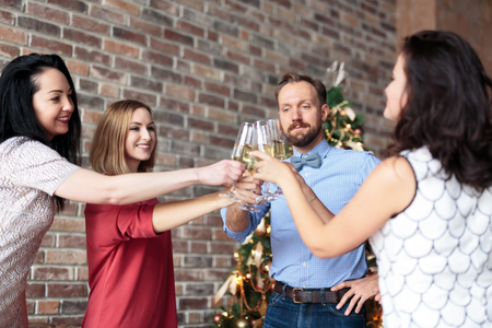 Young people clinking with champagne glasses while hanging out at New Years party