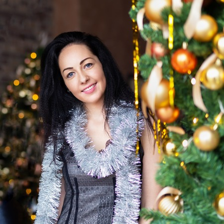 Close-up portrait of smiling brunette woman on New Years party near decotated Christmas tree