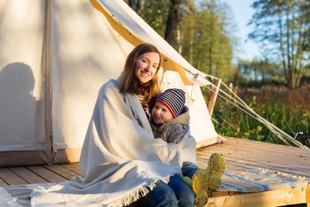 Young mother embracing her 3 years old kid with a blanket while sitting near canvas bell tent in a forest Banque d'images