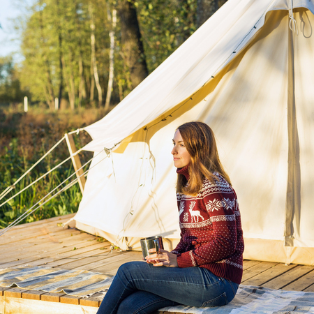 Young woman wearing warm jersey drinking cofee while sitting near a camping tent in the morning at the forest 免版税图像