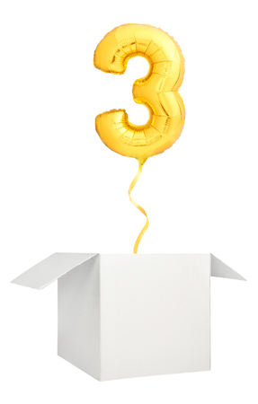 Golden number three inflatable balloon with golden ribbon flying out of blank white box isolated on white background