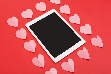Touchpad on red background with paper cut hearts. Tablet computer with blank screen for your copy. Valentines Day concept