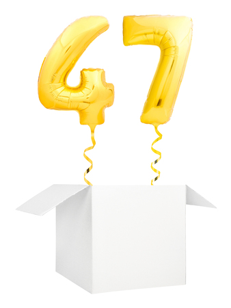 Golden number forty seven inflatable balloon with golden ribbon flying out of blank white box isolated on white background. Birthday concept.