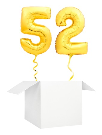 Golden number fifty two inflatable balloon with golden ribbon flying out of blank white box isolated on white background. Birthday concept. Banco de Imagens