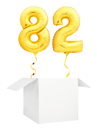 Golden number eighty two inflatable balloon with golden ribbon flying out of blank white box isolated on white background. Birthday concept. Standard-Bild