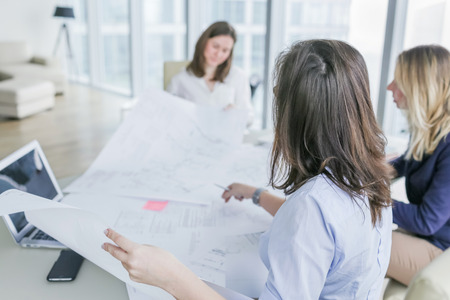 Young business women working on drawings, papers at the table in modern office. Shallow DOF