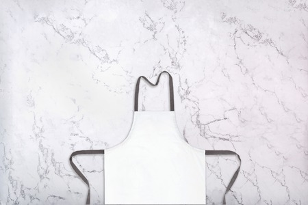 Crop of white kitchen apron on natural marble texture. Blank apron on marble background. Top view